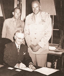 Harry S Truman signing Public Law 80-557 while two Civil Air Patrol members stand behind him